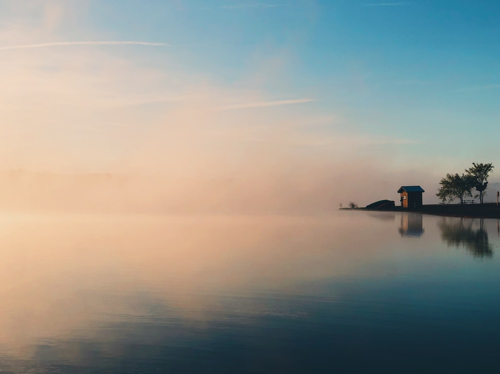 brown house beside large calm body of water