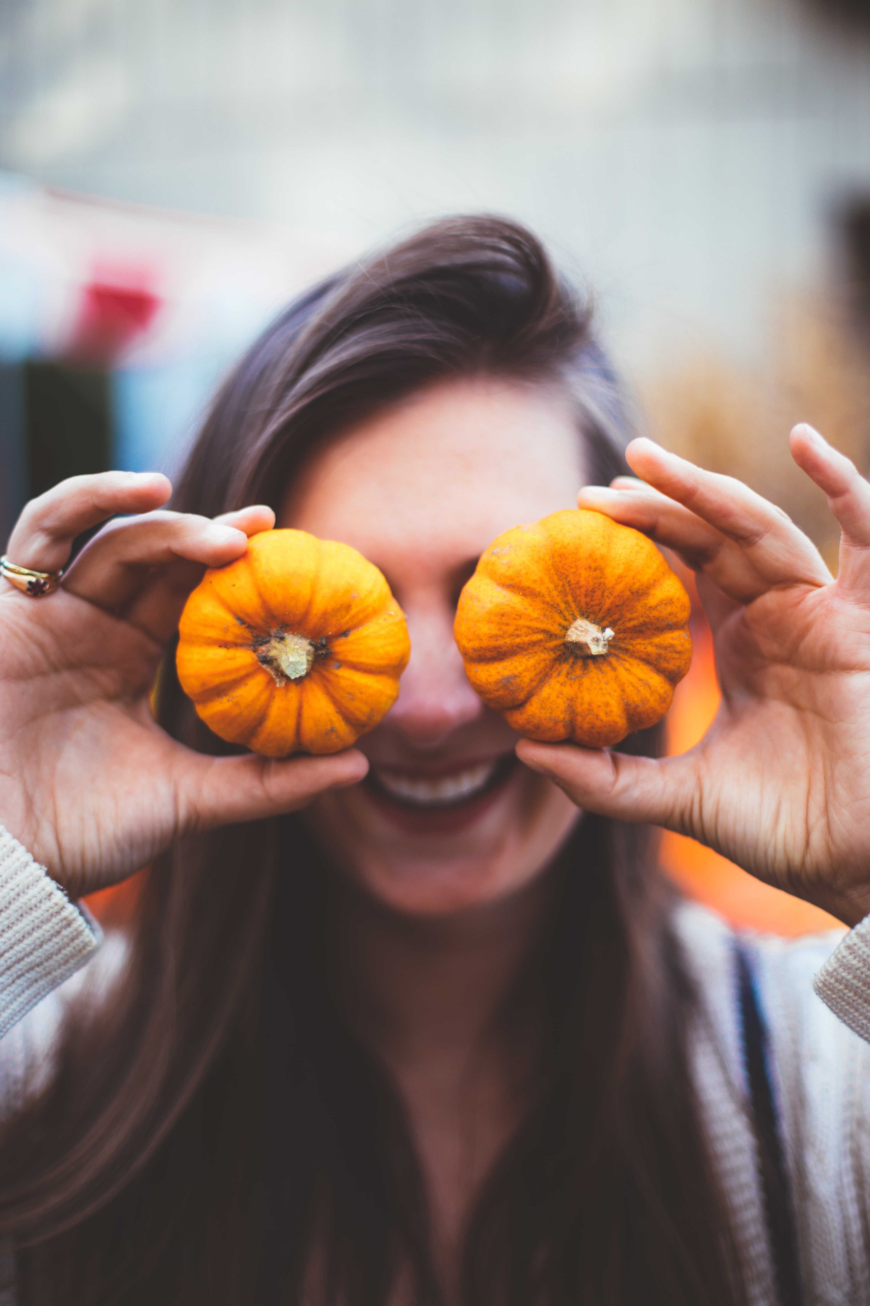 woman holding two orange pumpkins covering her eyes