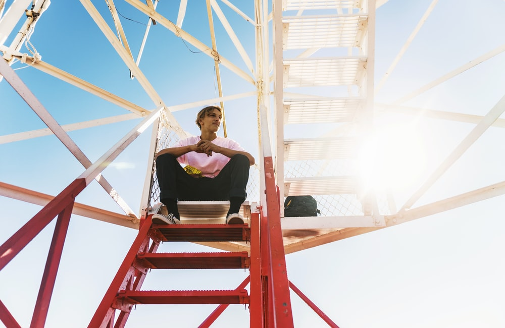 man sitting on red staircase