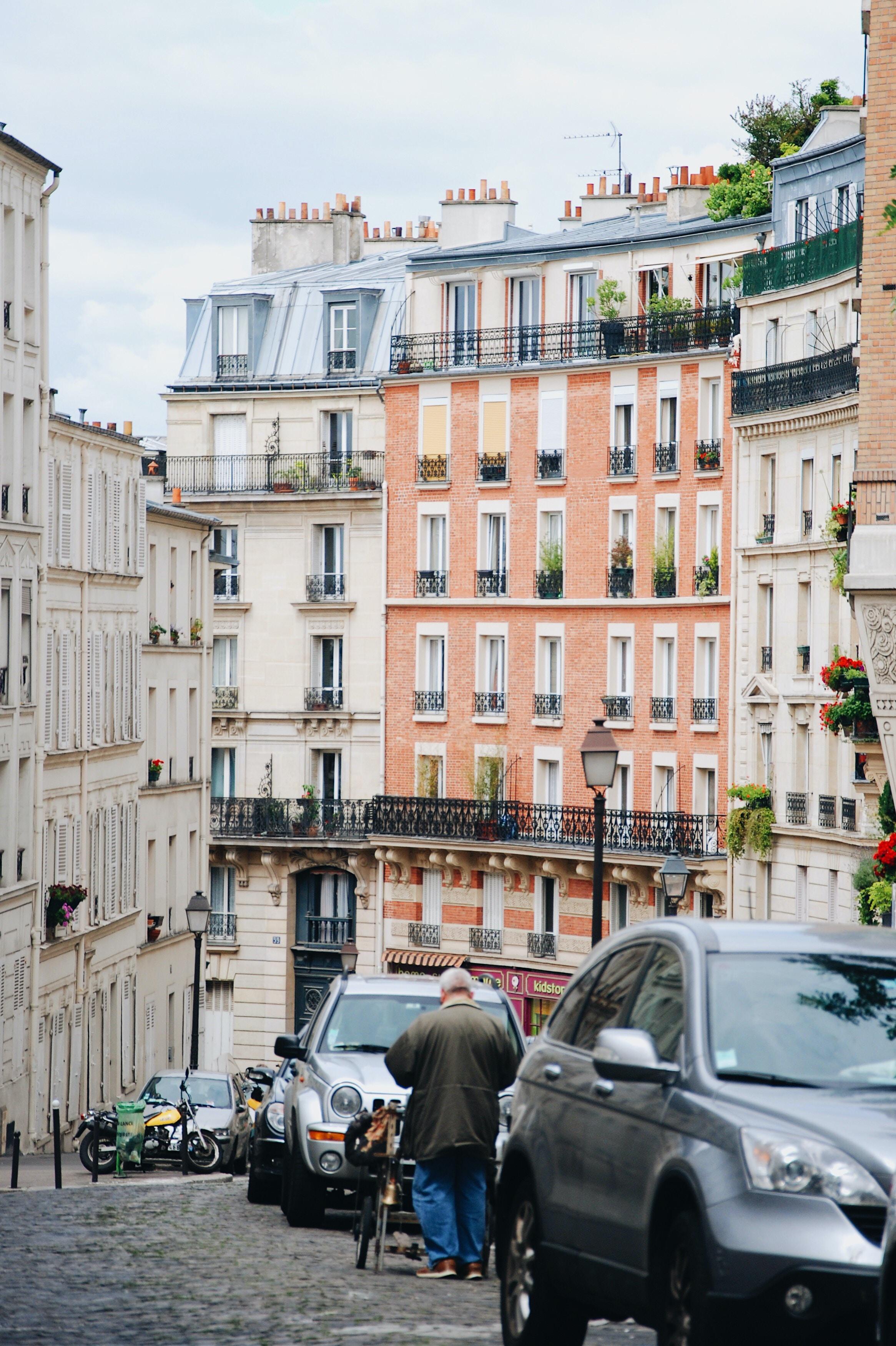 man walking beside gray vehicle\