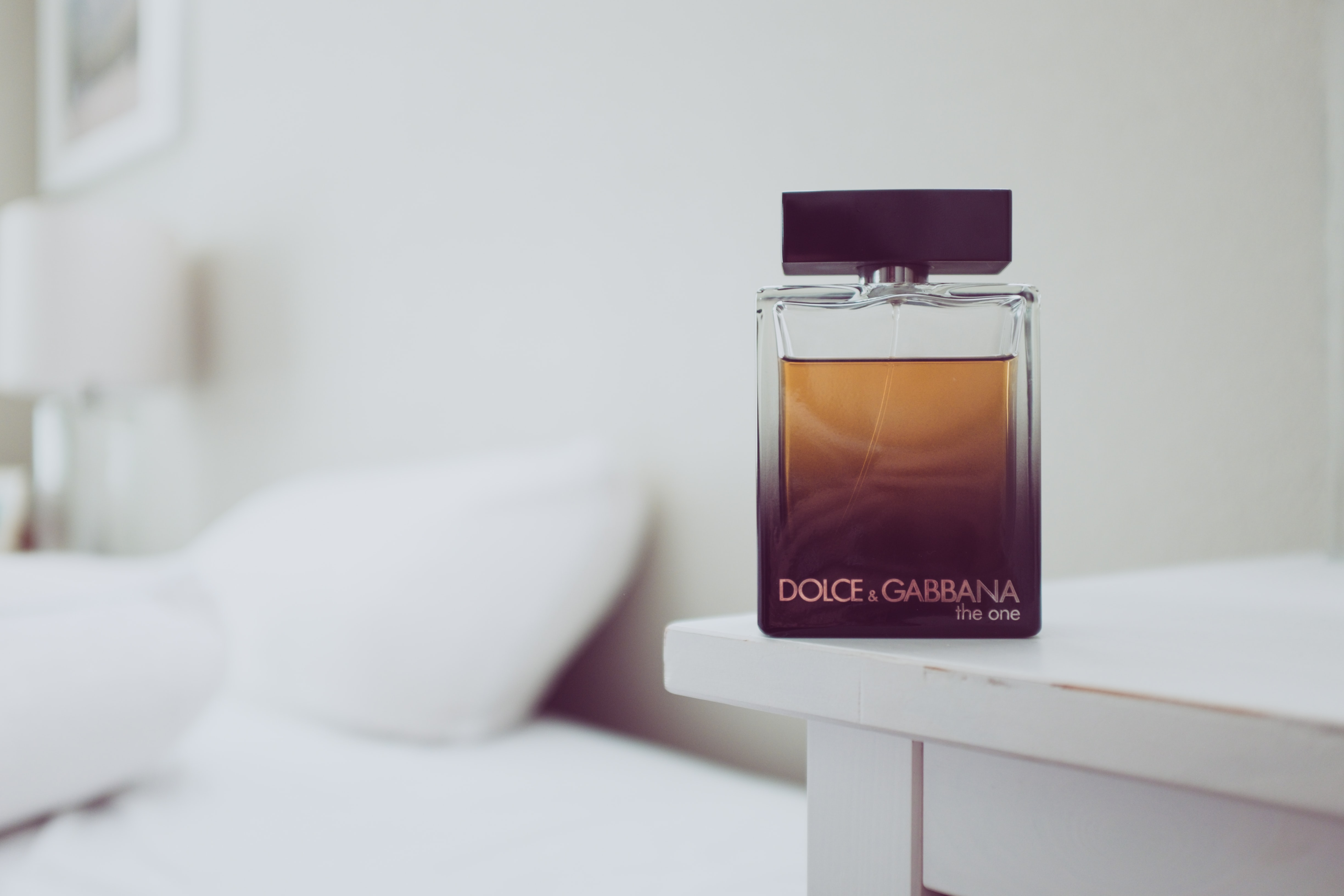Dolce & Gabbana The One fragrance bottle on white wooden table