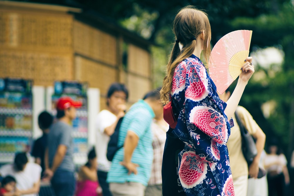 selective focus photography of woman holding hand fan beside road