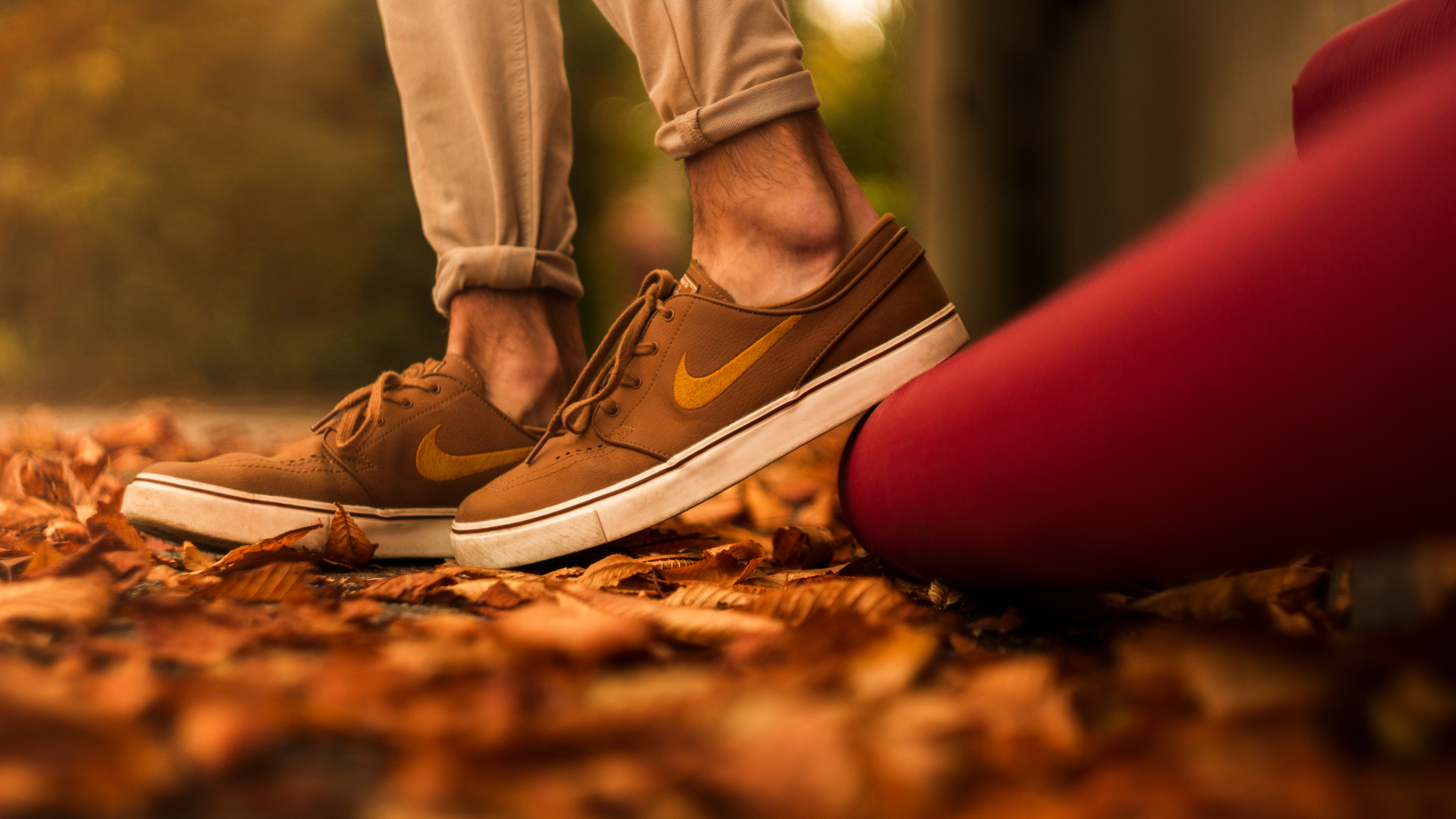 low-angle photo of person wearing pair of brown Nike sneakers