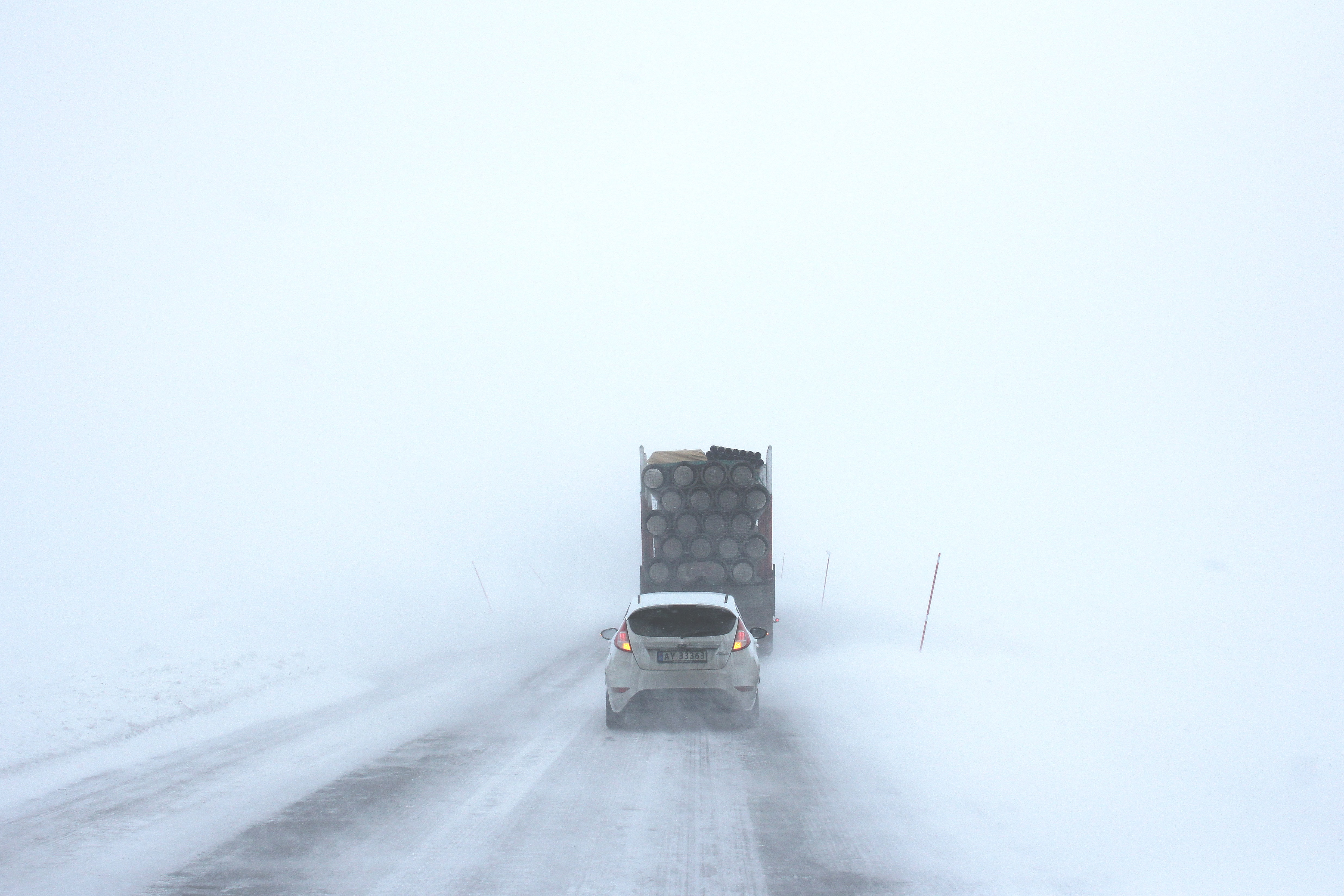 white car behind a truck on snowy road