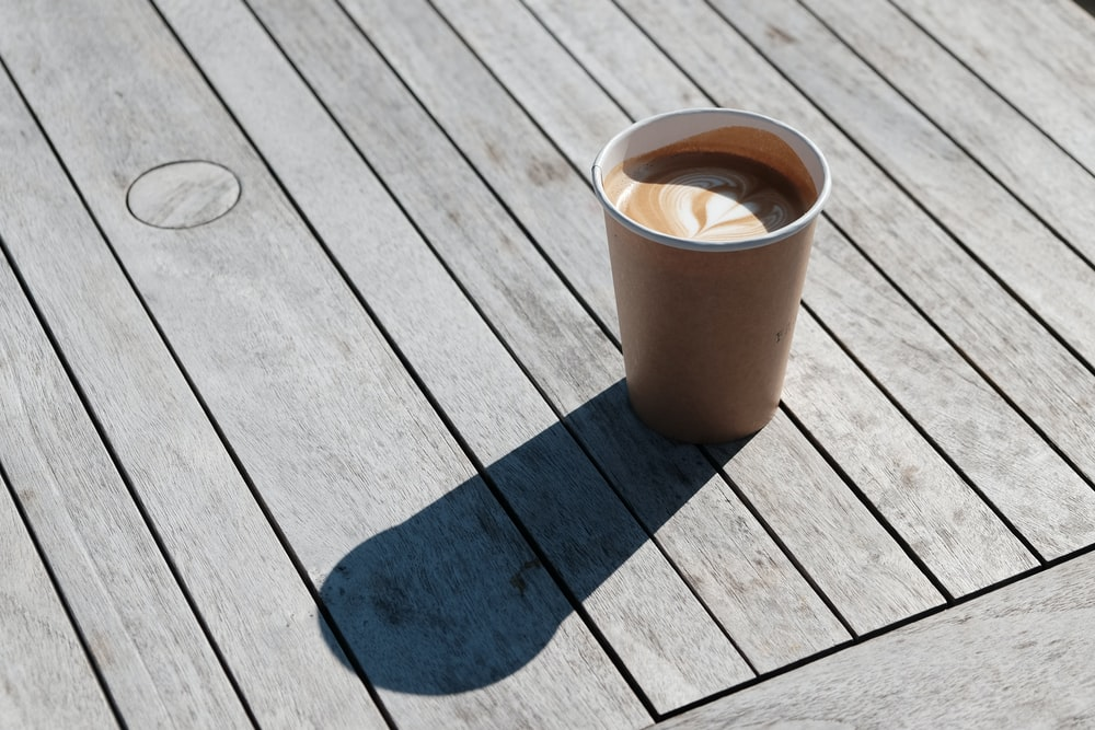 cappuccino on grey wooden planks at daytime