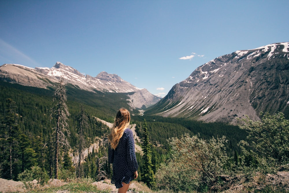 woman standing in front of mountain range under clear blue sky during daytime
