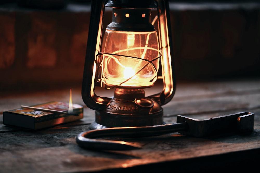 lantern beside black metal hook on brown furniture