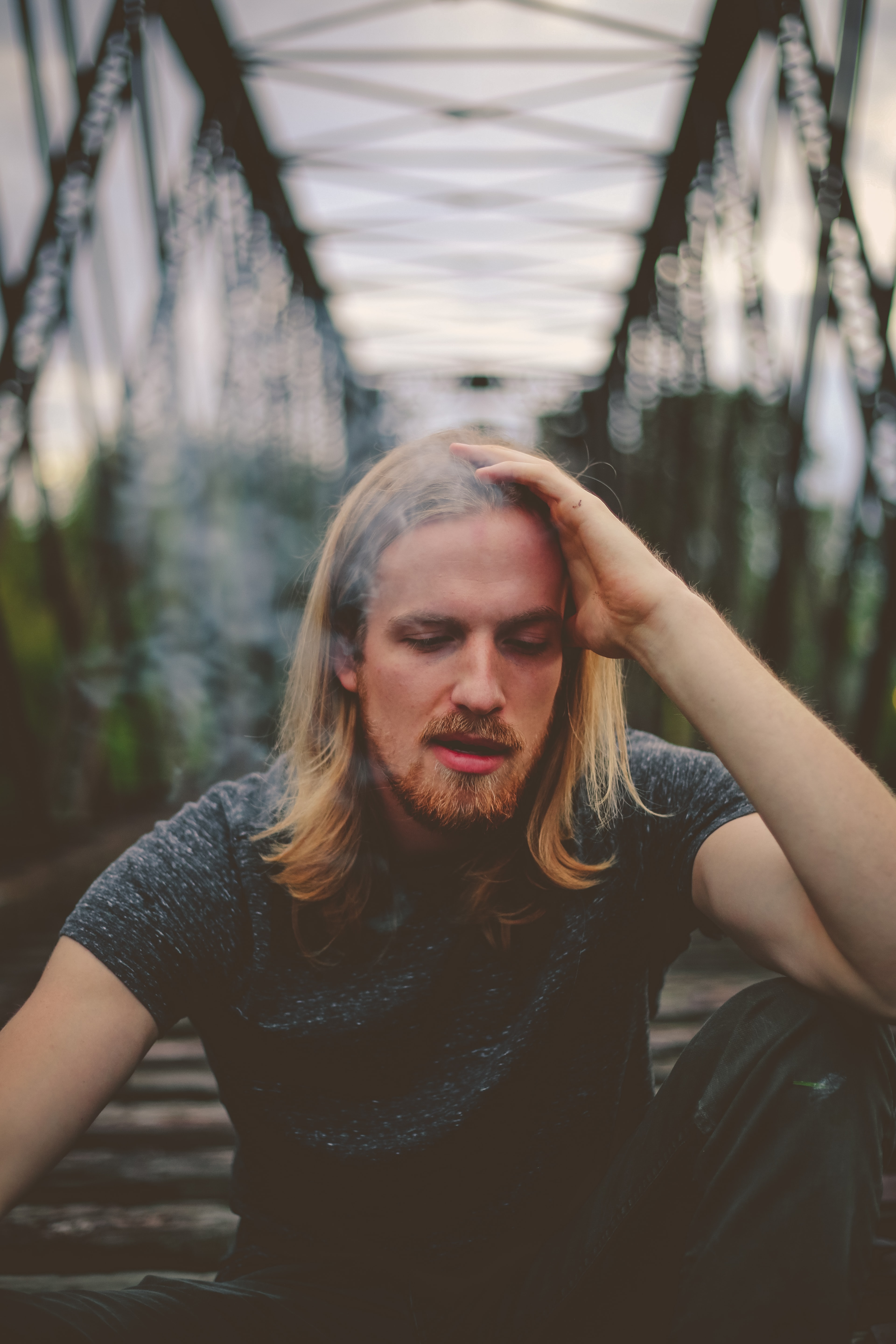 shallow focus photography of man sitting on bridge during day