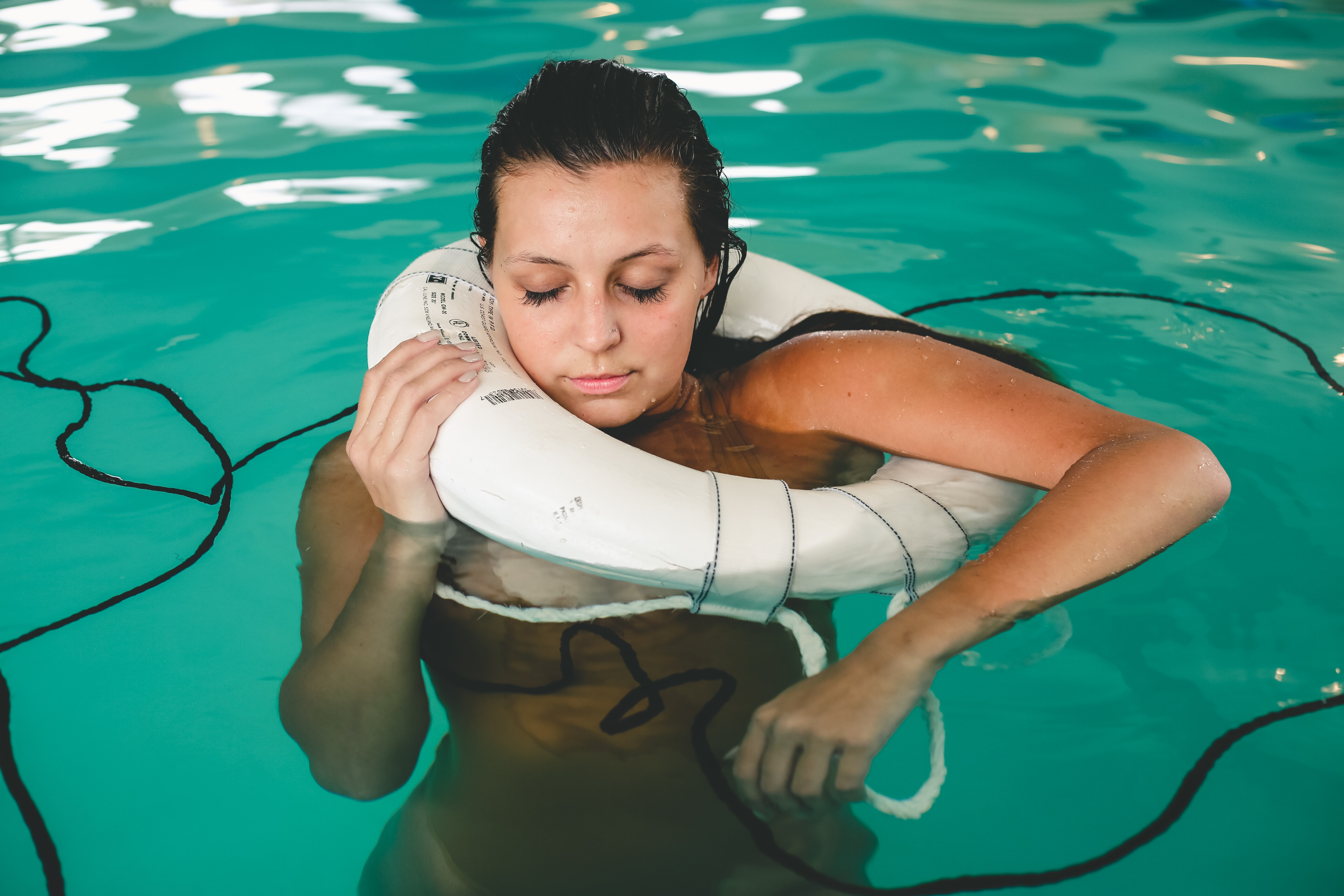 woman floating on swimming pool while holding a white buoy