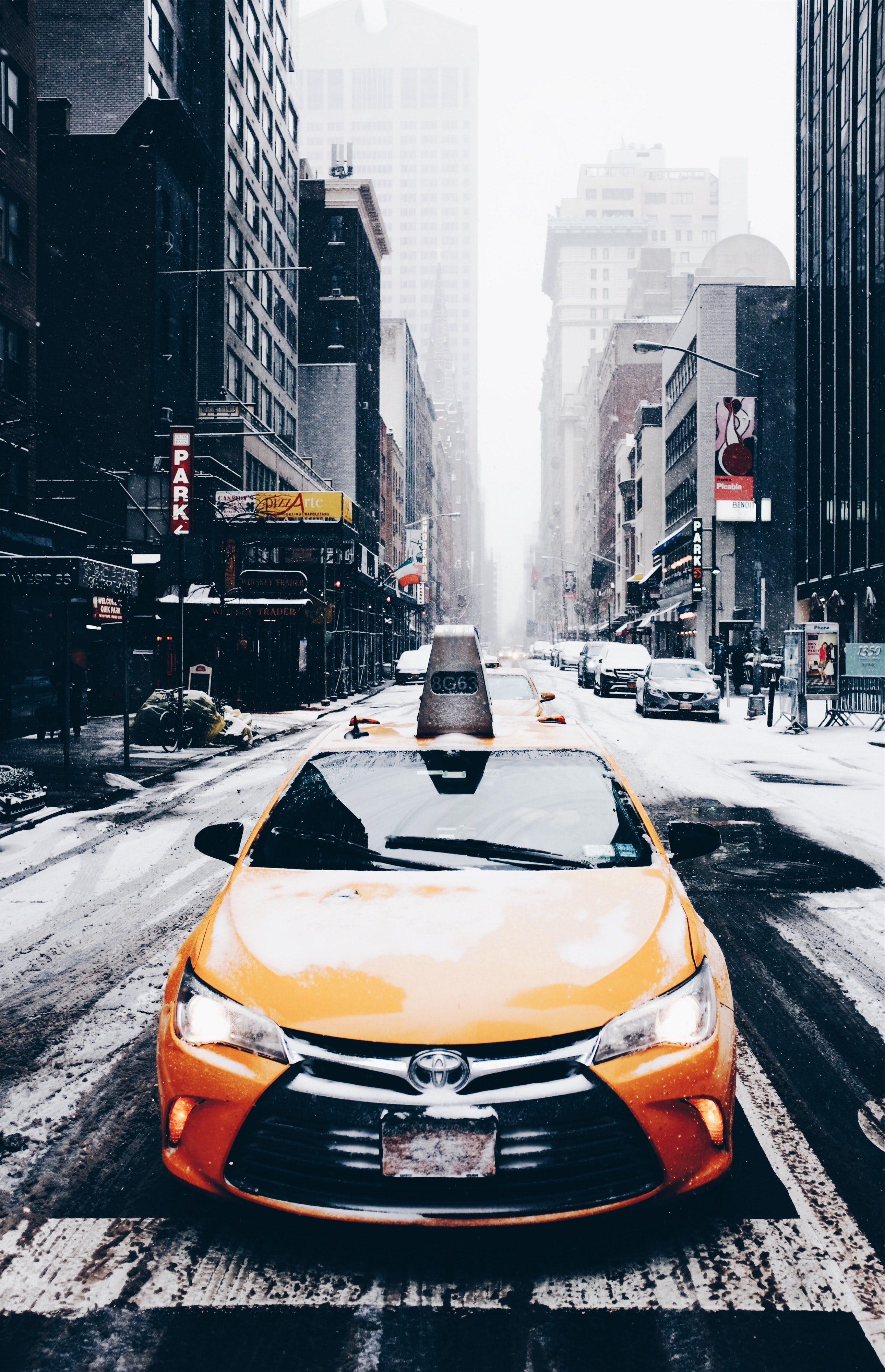 orange Toyota car on road near buildings