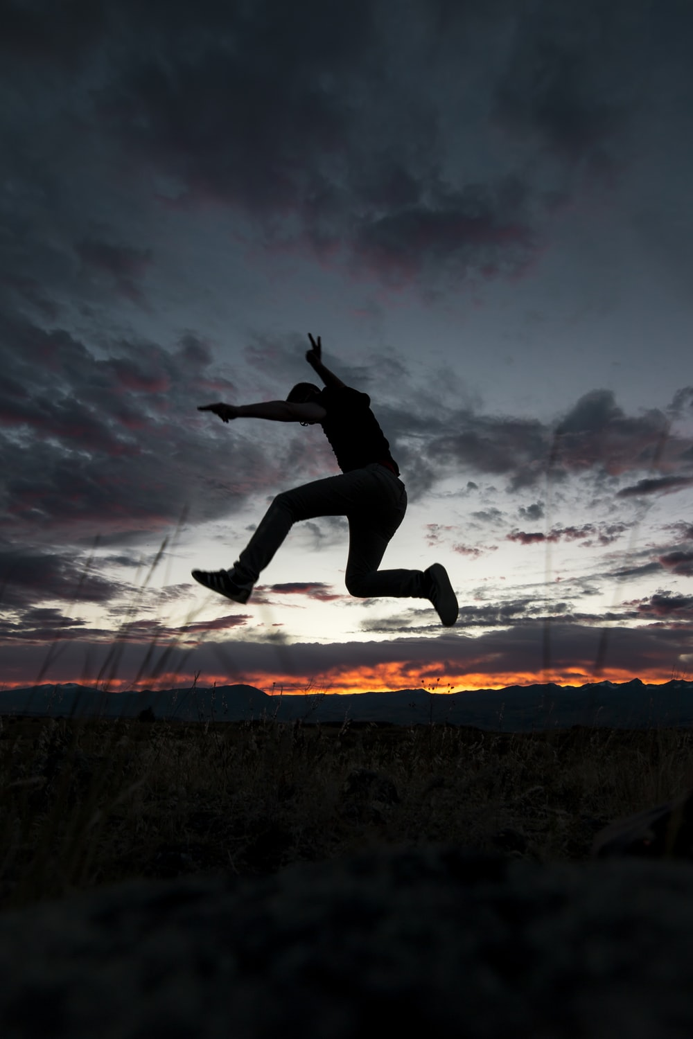 man leaping above ground under cloudy skies golden hour photography
