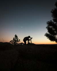silhouette photography of man capturing photo during night time