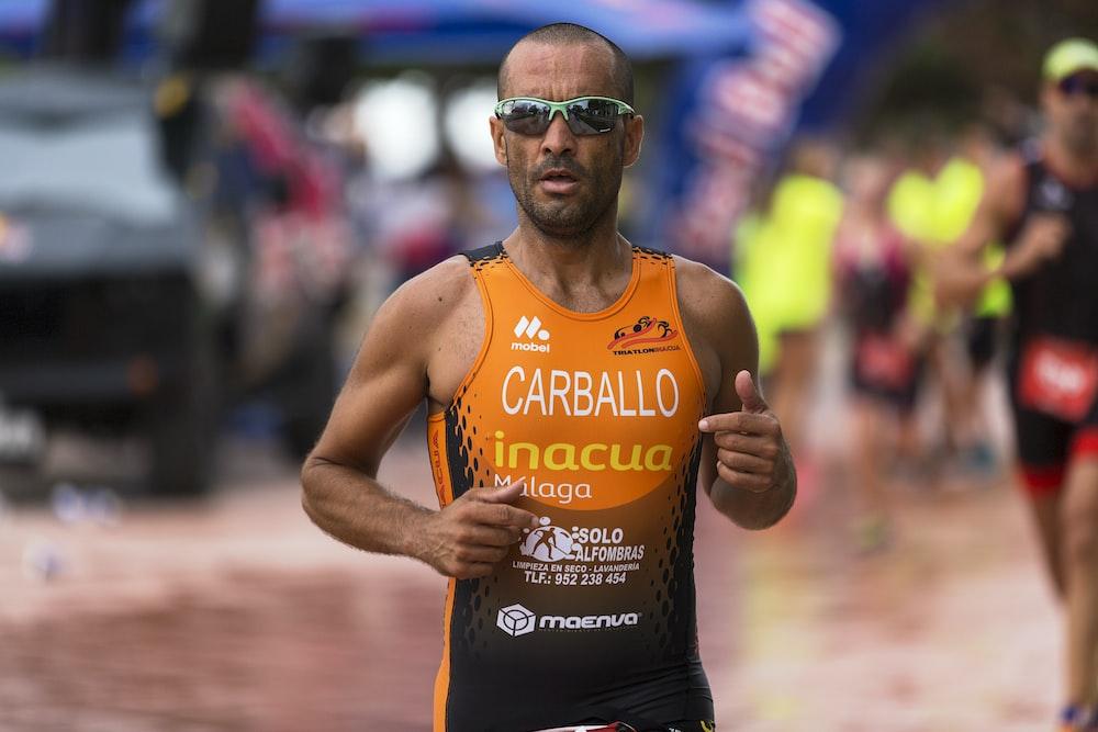 man wearing orange tank top and gray framed sport sunglasses