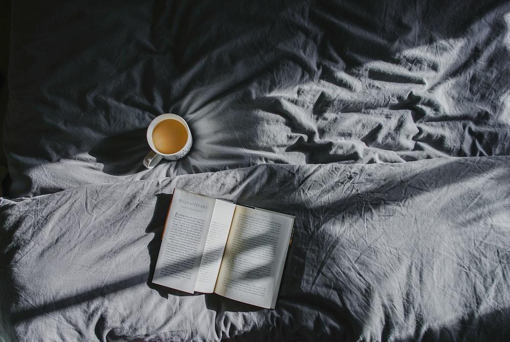 white ceramic mug beside book on gray textile