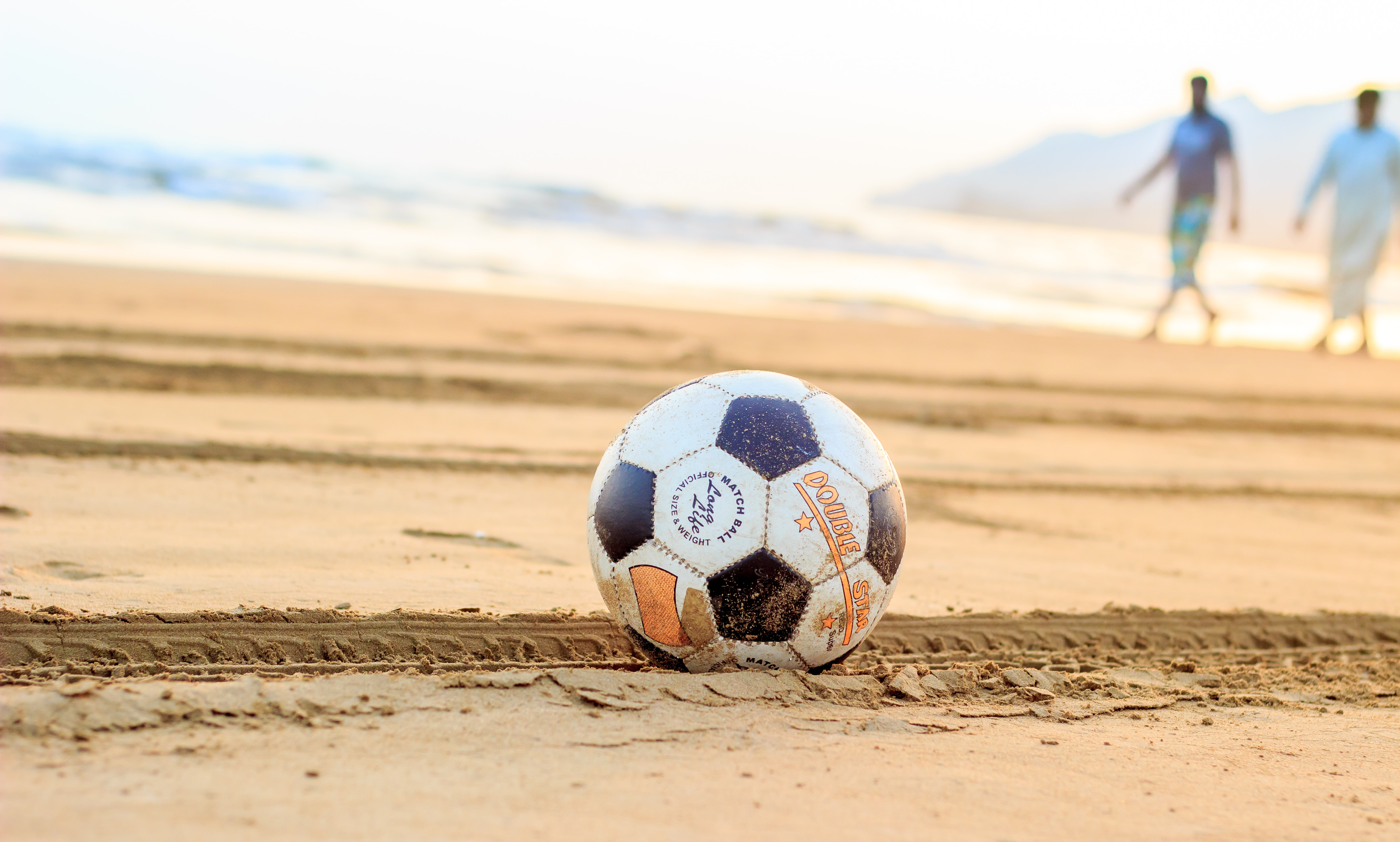 soccer ball on brown sand with two man in the background