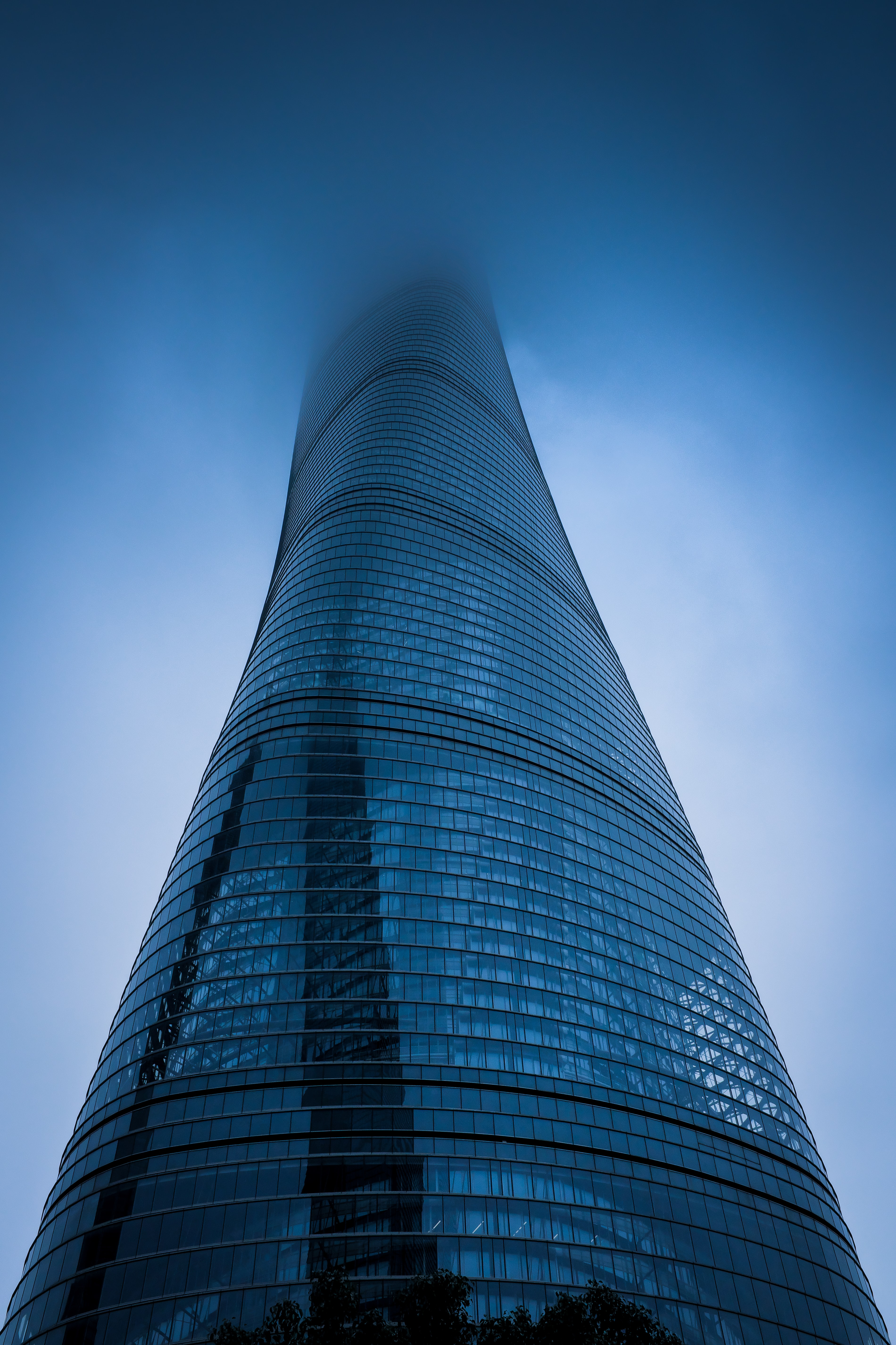 low angle photography of gray curtain wall building covered with fog