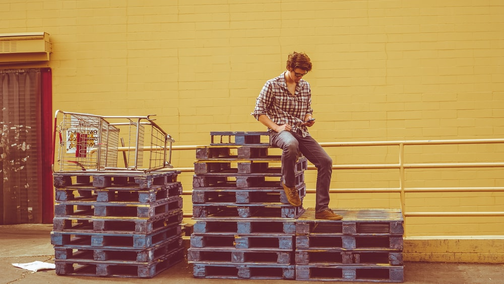 man sitting on top of pallets stack