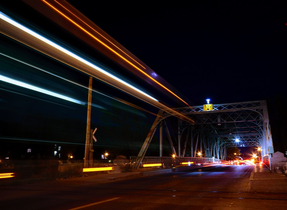 time lapse photography of vehicles crossing suspension bridge