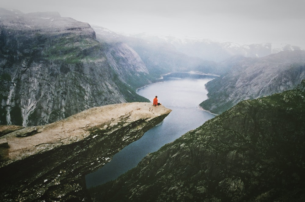 person wearing red shirt sitting on the boulder near the mountain