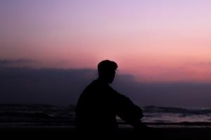 silhoutte of man sitting on ground