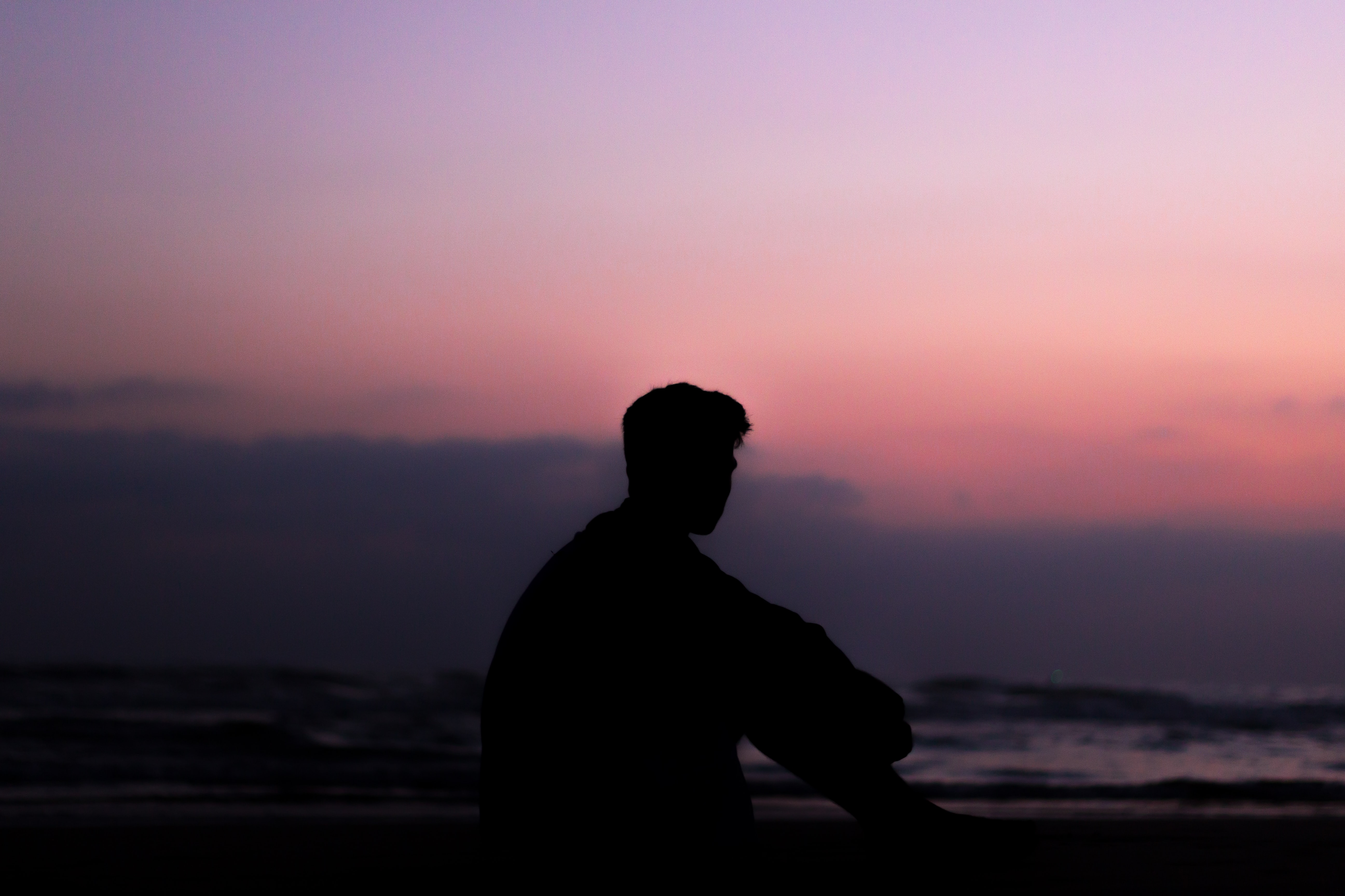 silhoutte of man sitting on ground