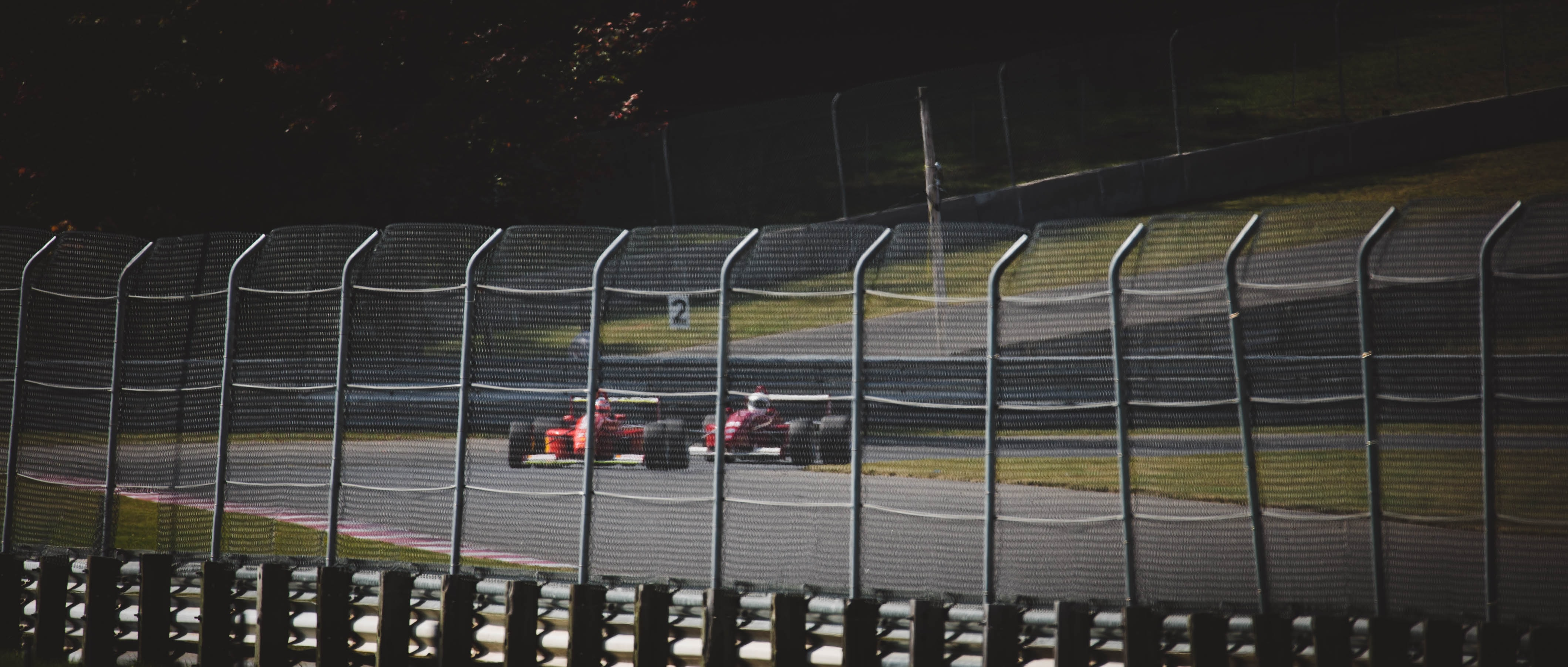 two red F1 cars on gray racetrack during daytime