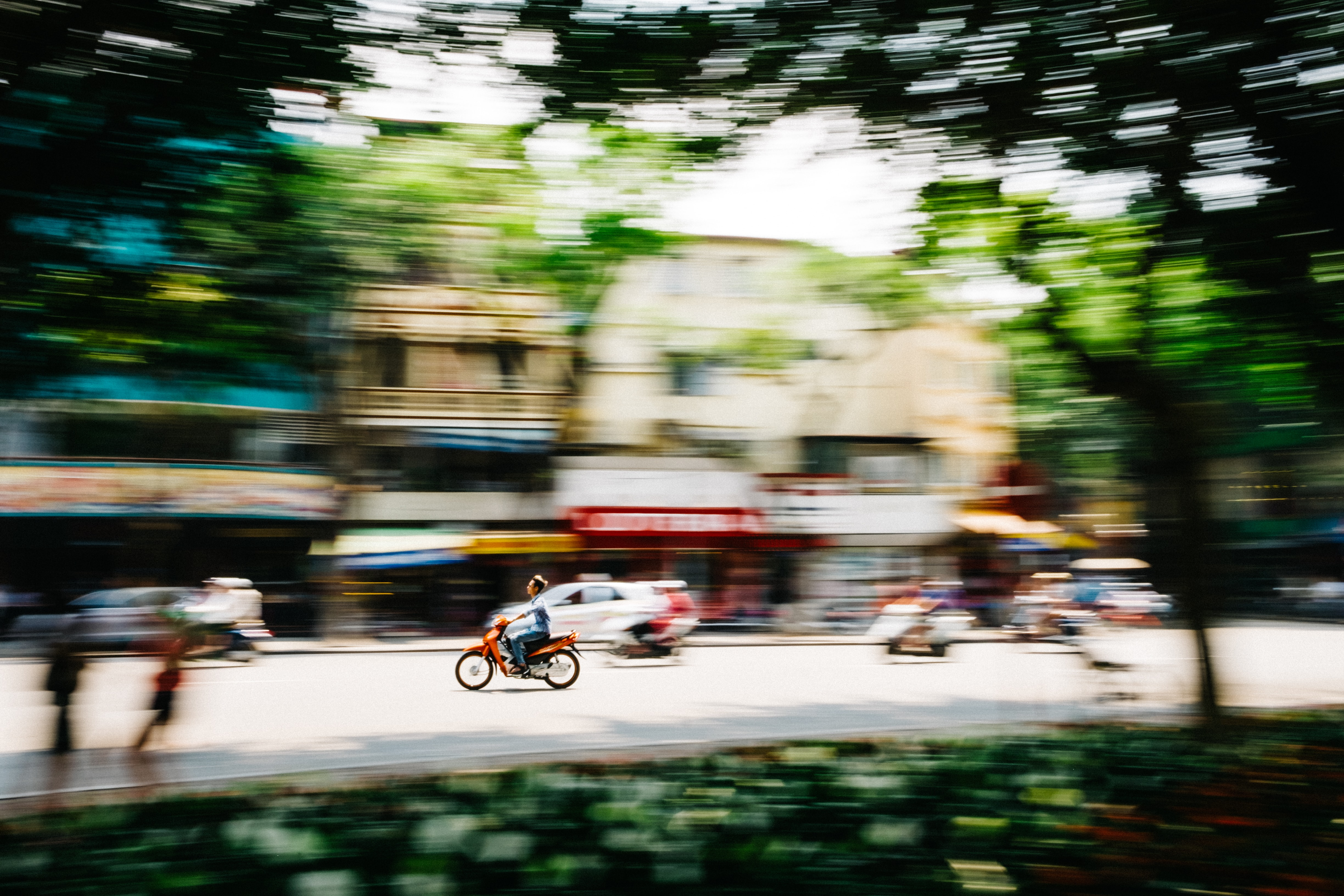 tilt shift photography of man riding motorcycle