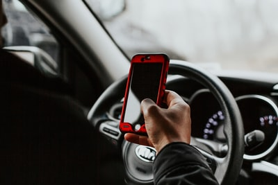 person holding red smartphone sitting in front of vehicle steering wheel