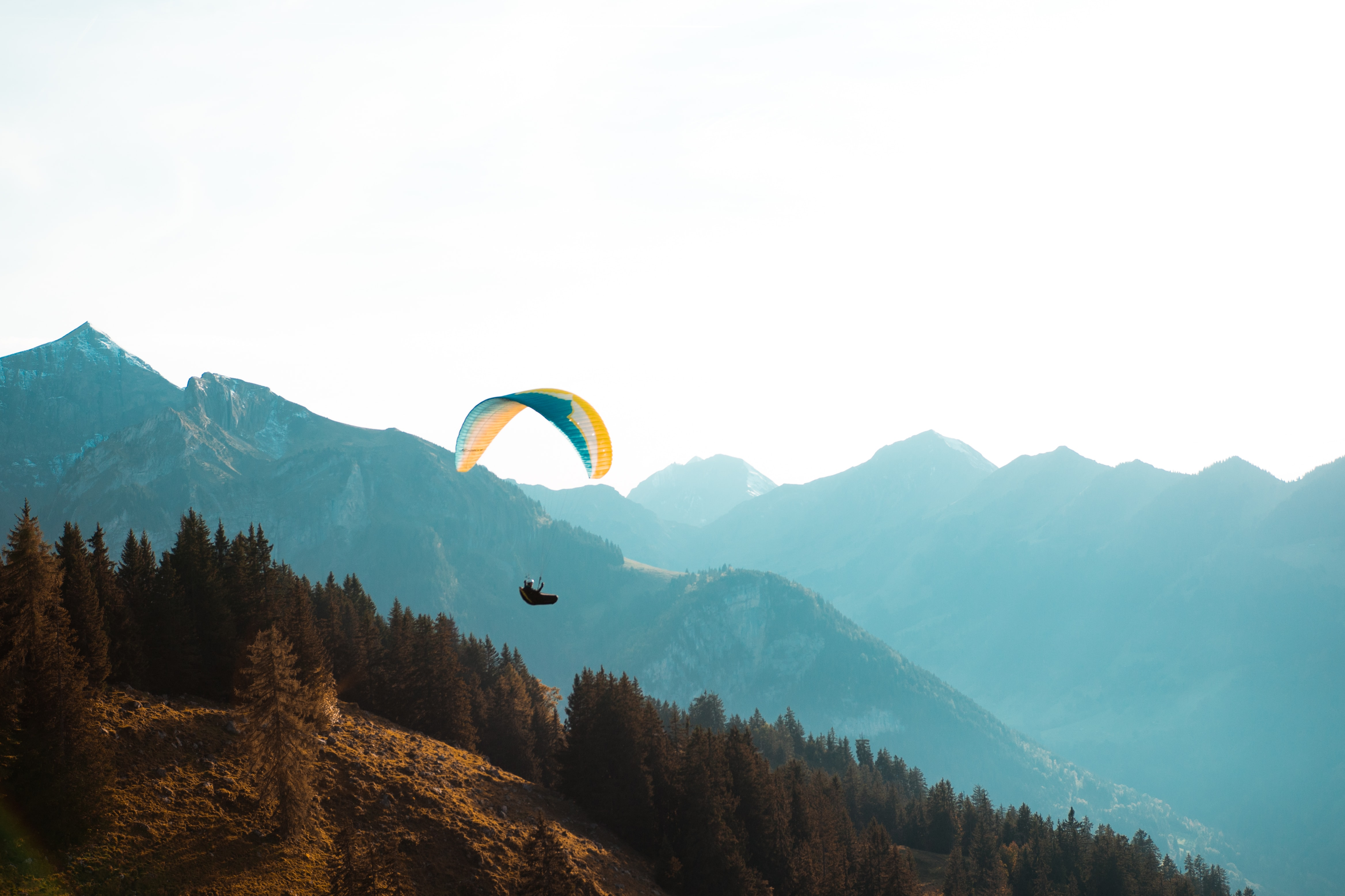 person paragliding near mountain at daytime