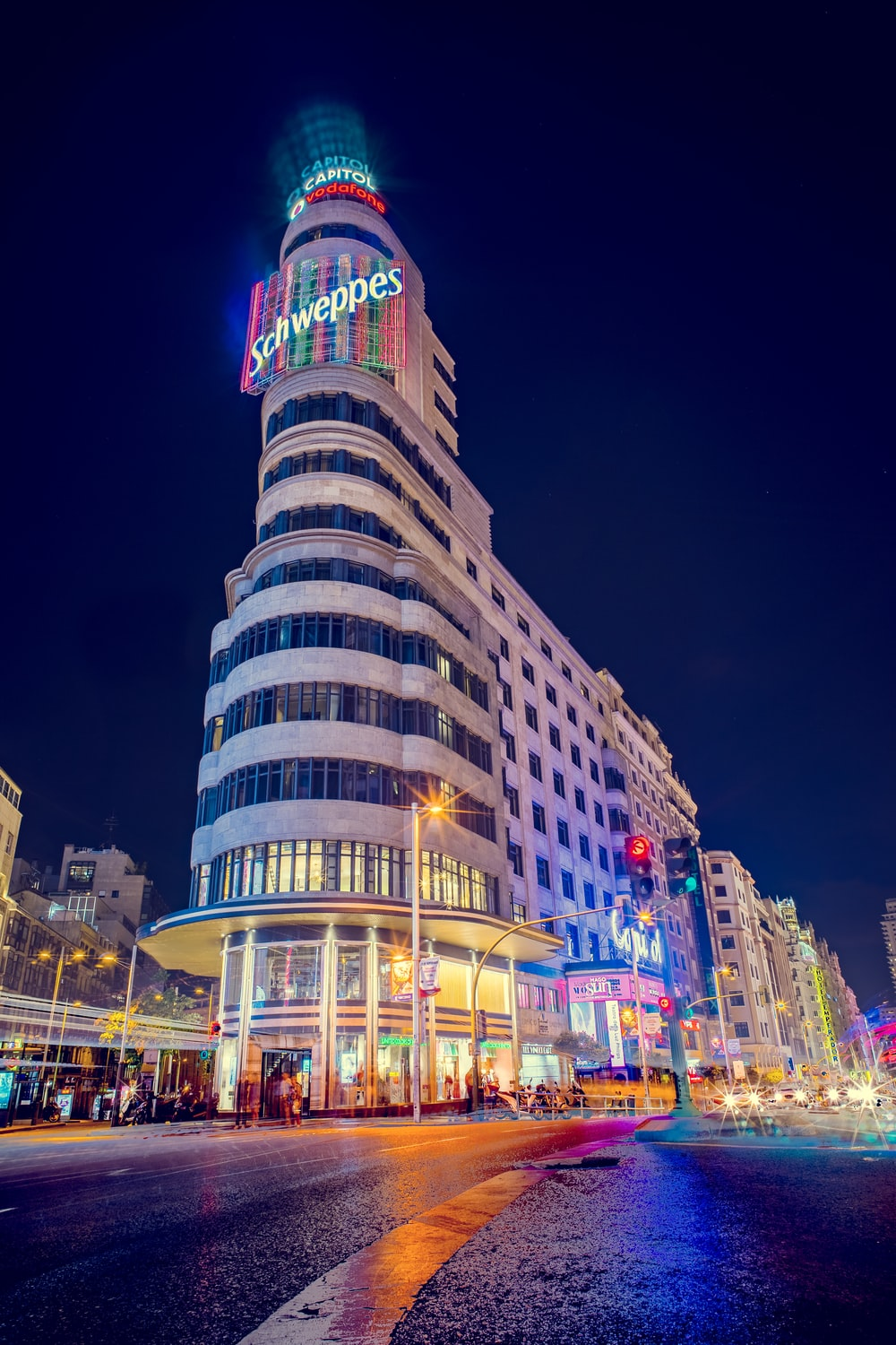 gray Schweppes building turn-on lights during night time