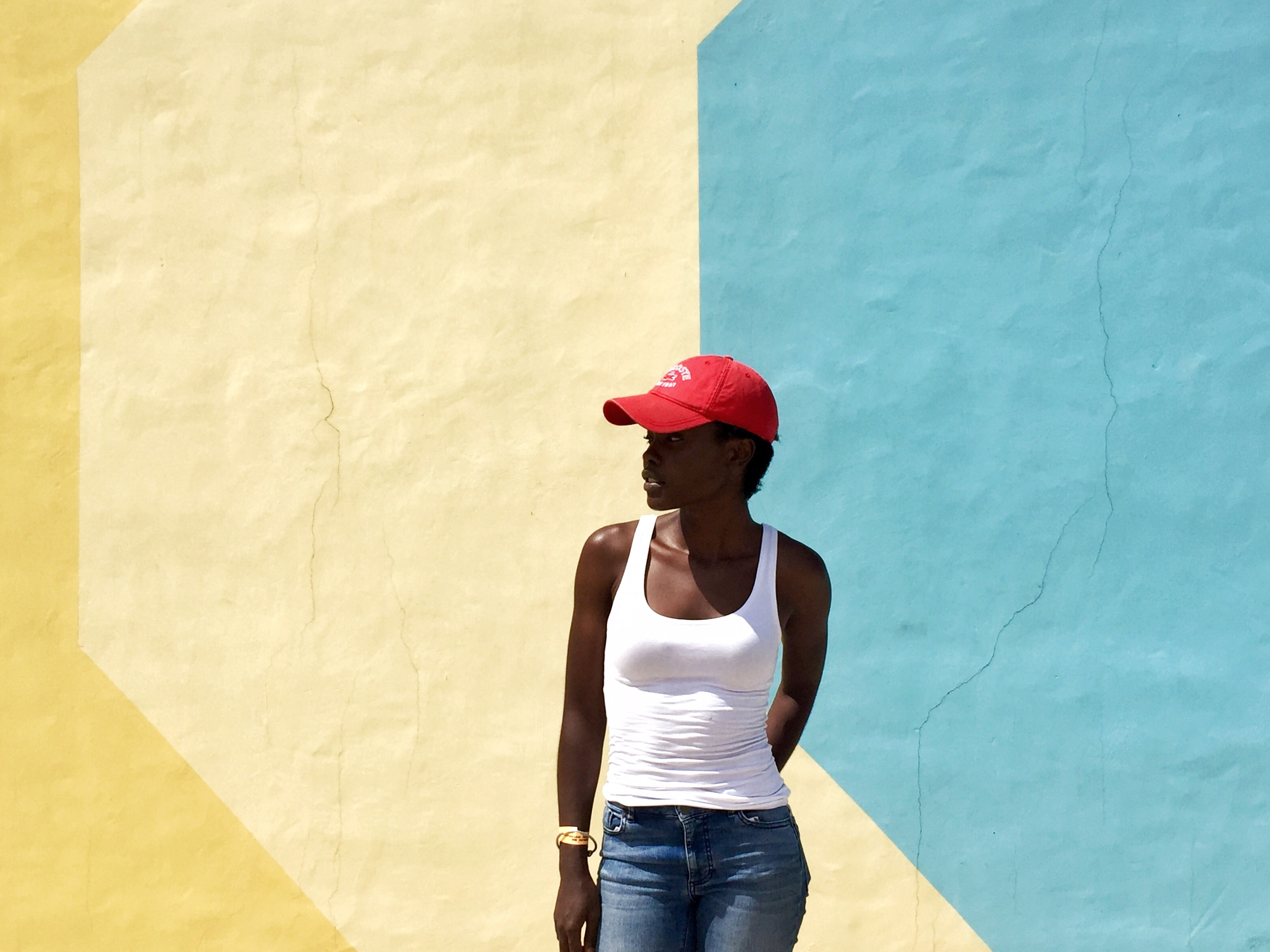 woman wearing white tank top standing next to beige and blue painted wall during daytime