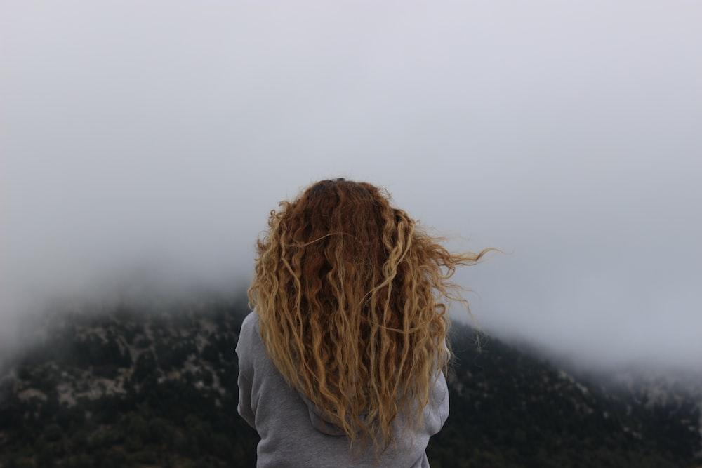 woman wearing gray shirt facing fog-covered green mountain photo