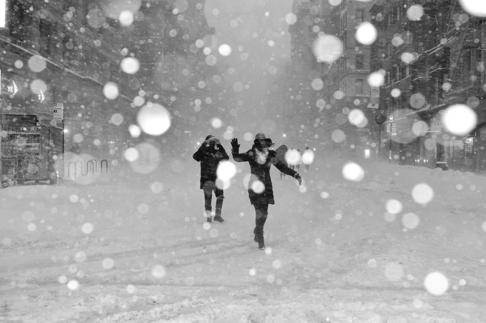 people walking on snow covered street with bokeh effects photo