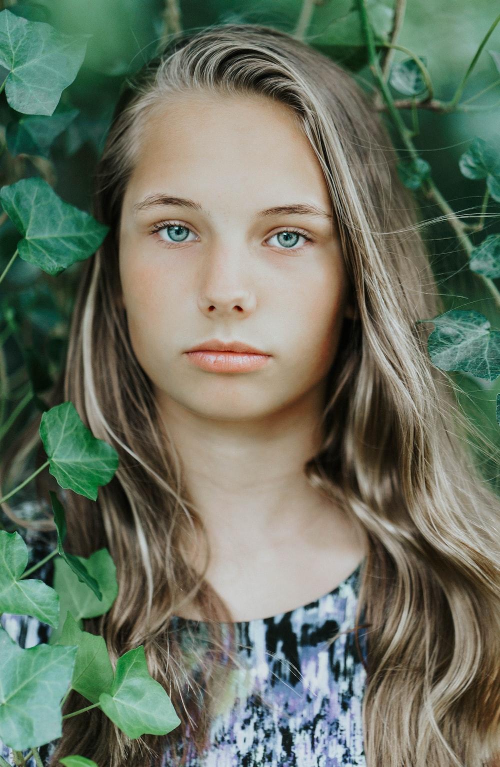 girl behind green vines