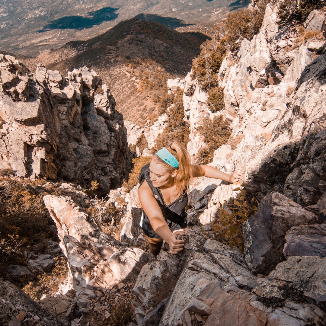 A strong woman climbing a mountain.