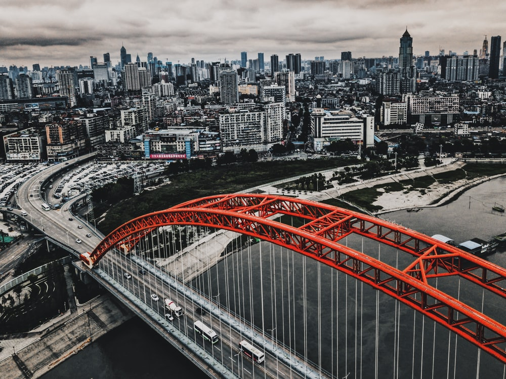 selective color photography of top angle vehicle on suspension bridge near city