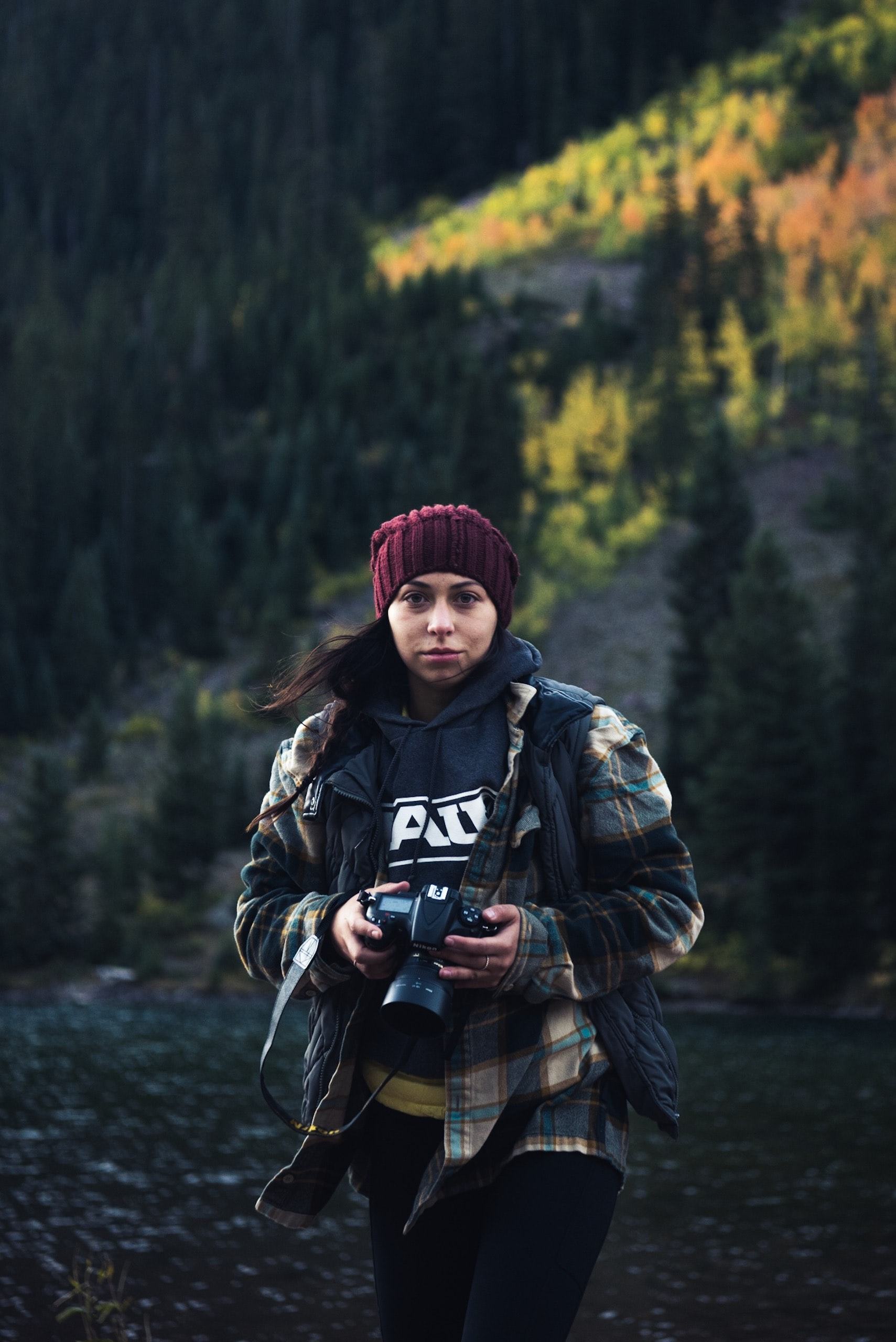 women wearing jacket and red knit cap holding DSLR camera walking near trees