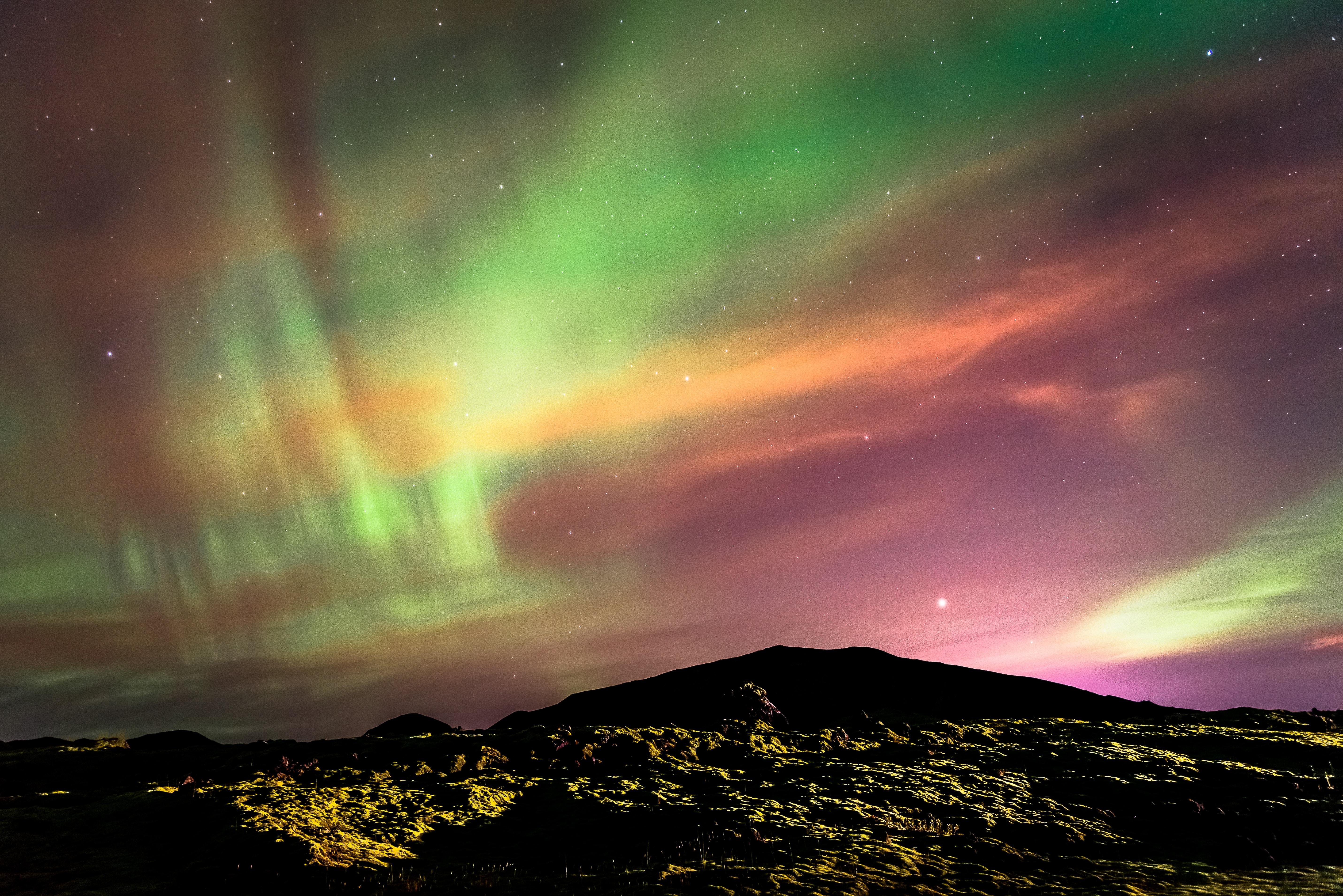 silhouette of mountain during aurora borealis long exposure photography