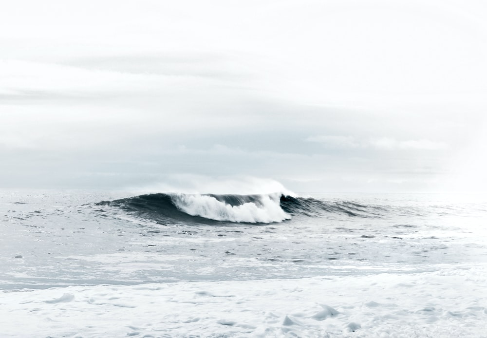waves under cloudy sky during daytime
