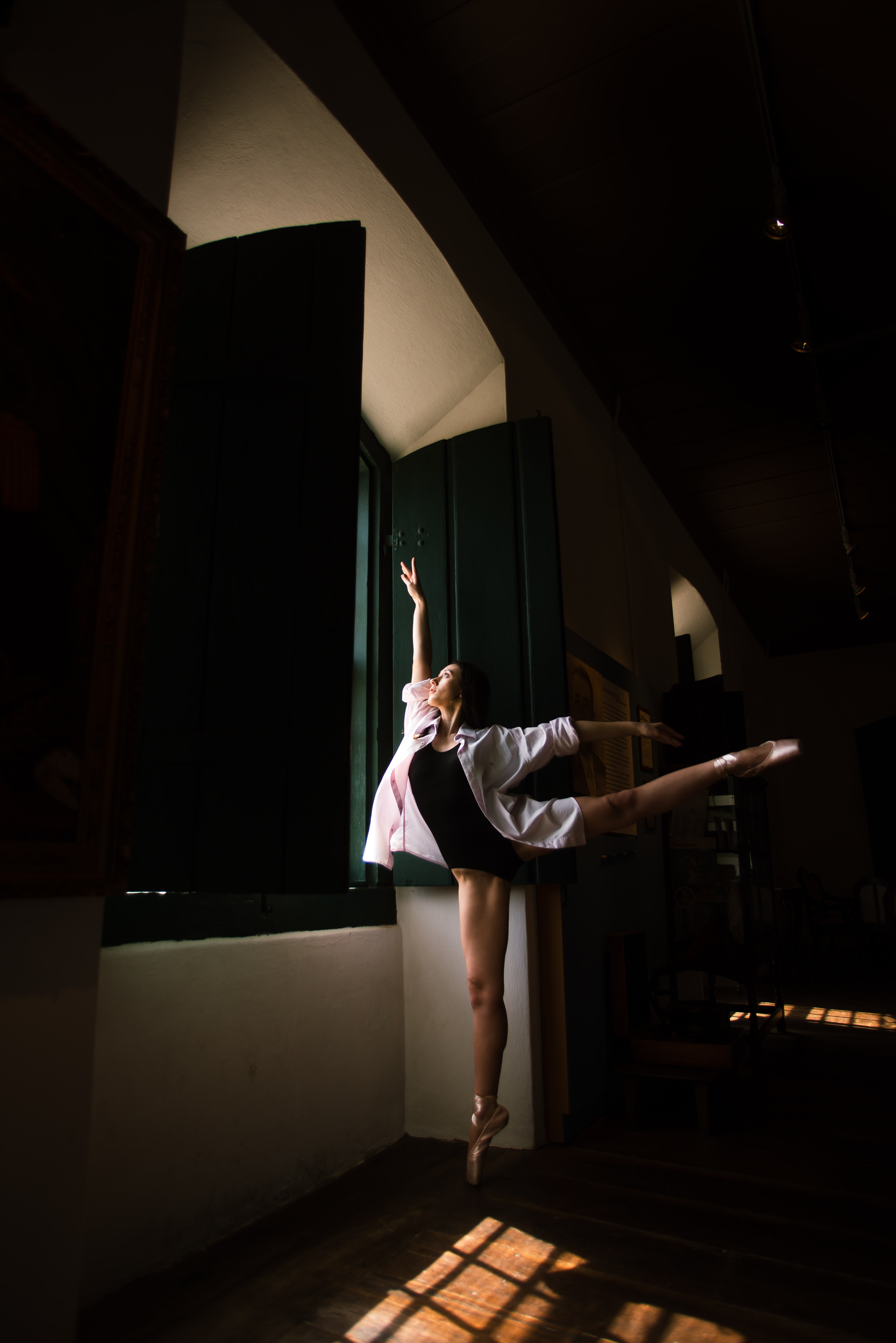woman doing ballet pose in front of window during daytime