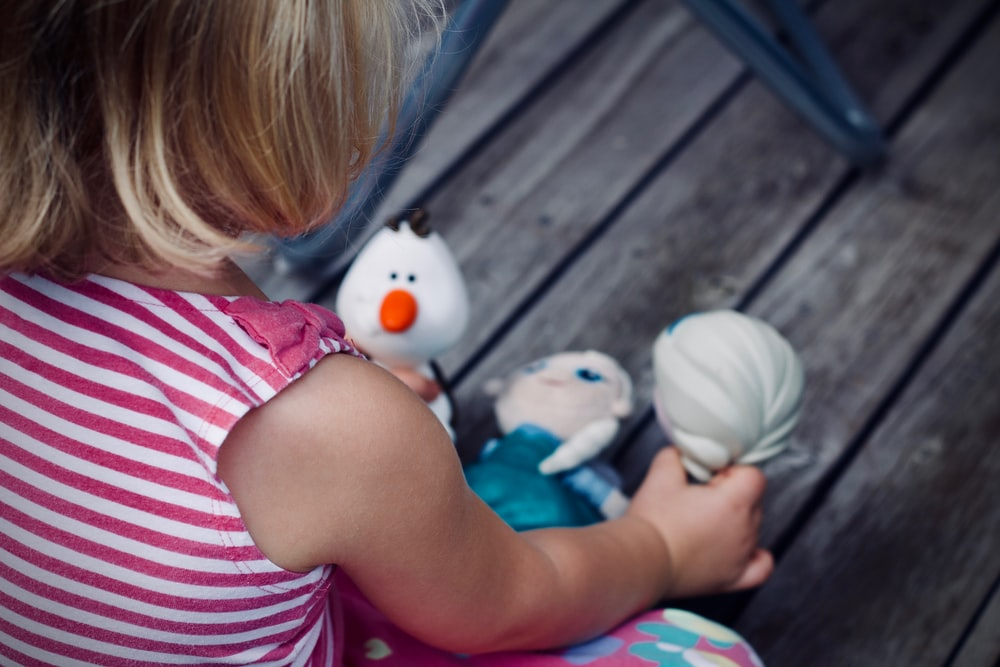 girl playing Disney Frozen character toy