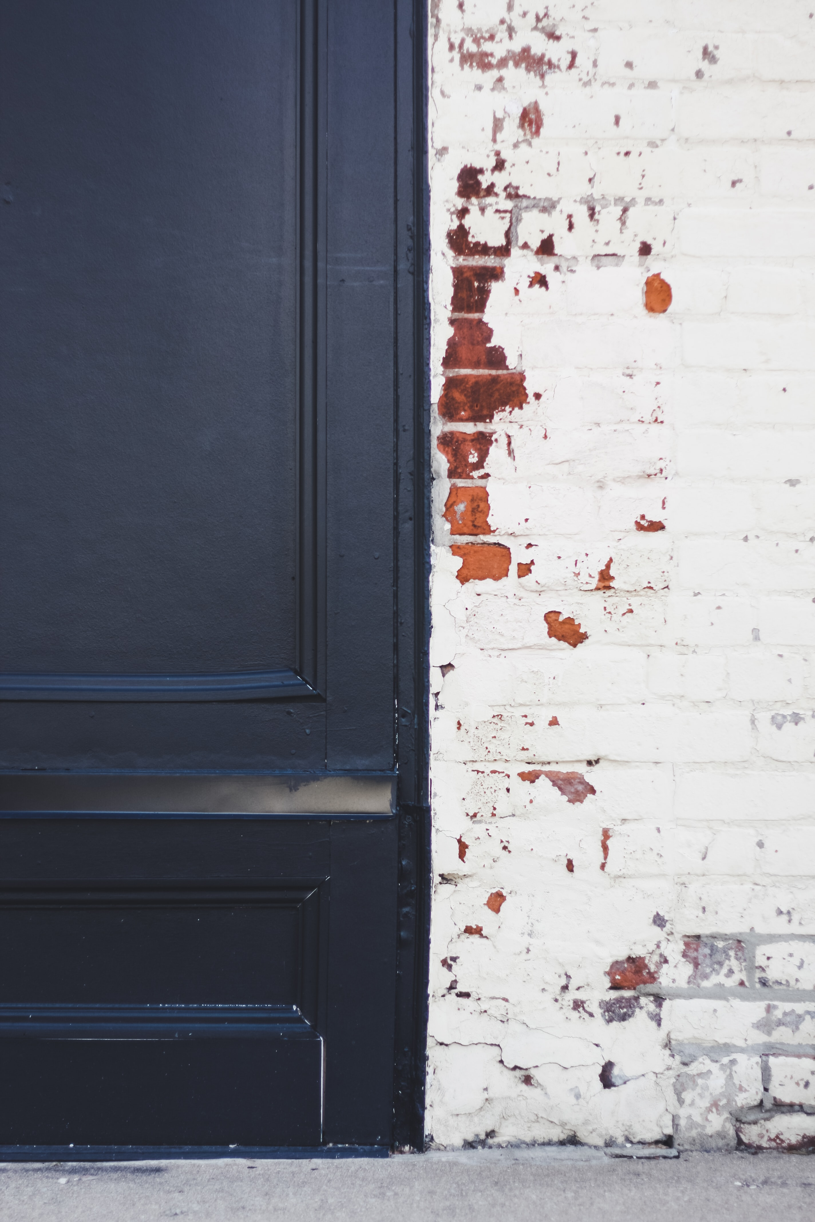 blue wooden door beside white and brown wall