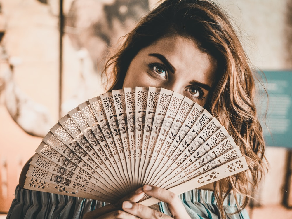 photography of woman holding brown hand fan