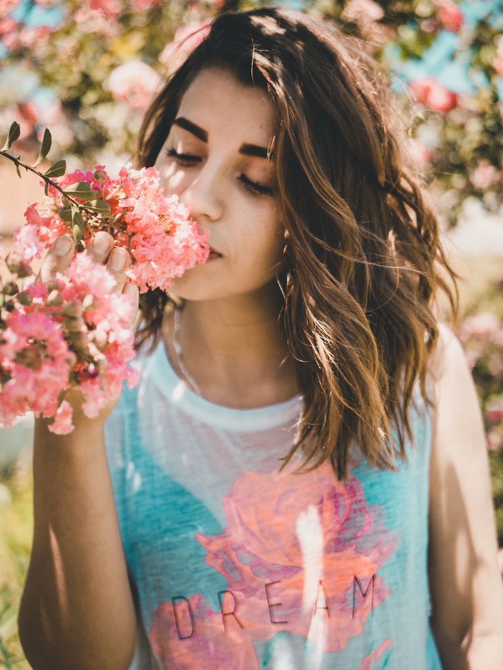 woman smelling pink flowers