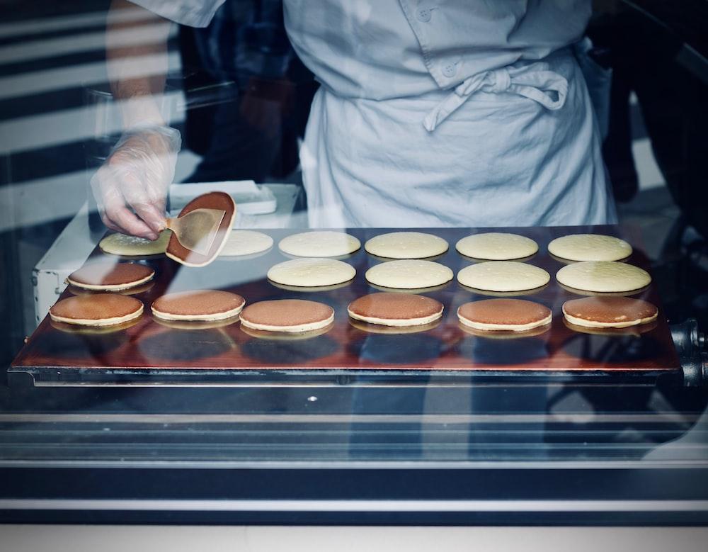 person in white apron baking flatbread