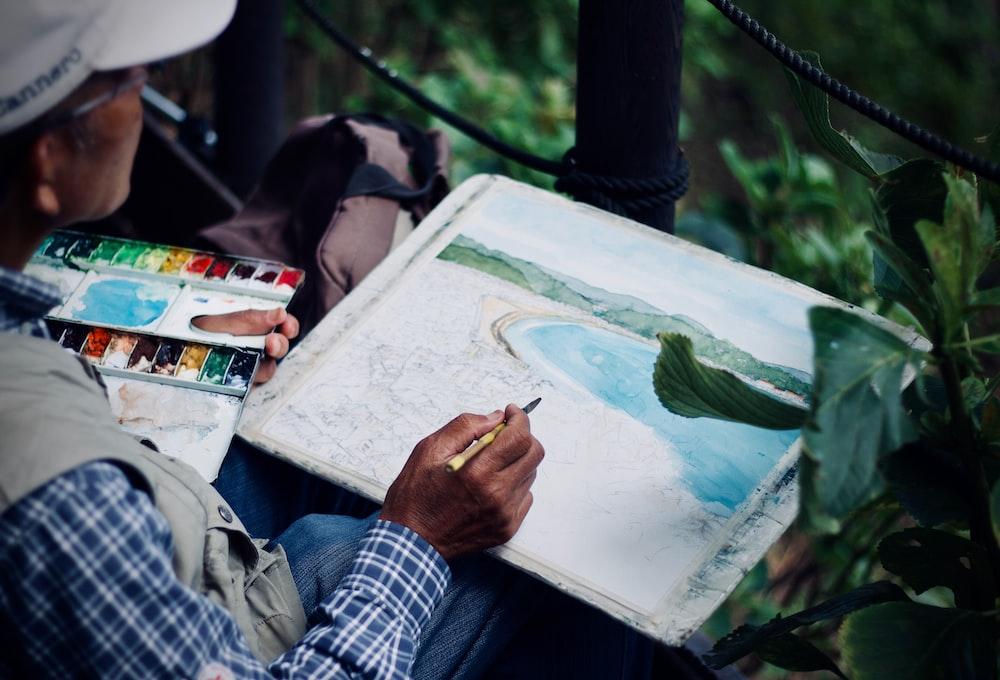 man holding brown and black pen painting seashore