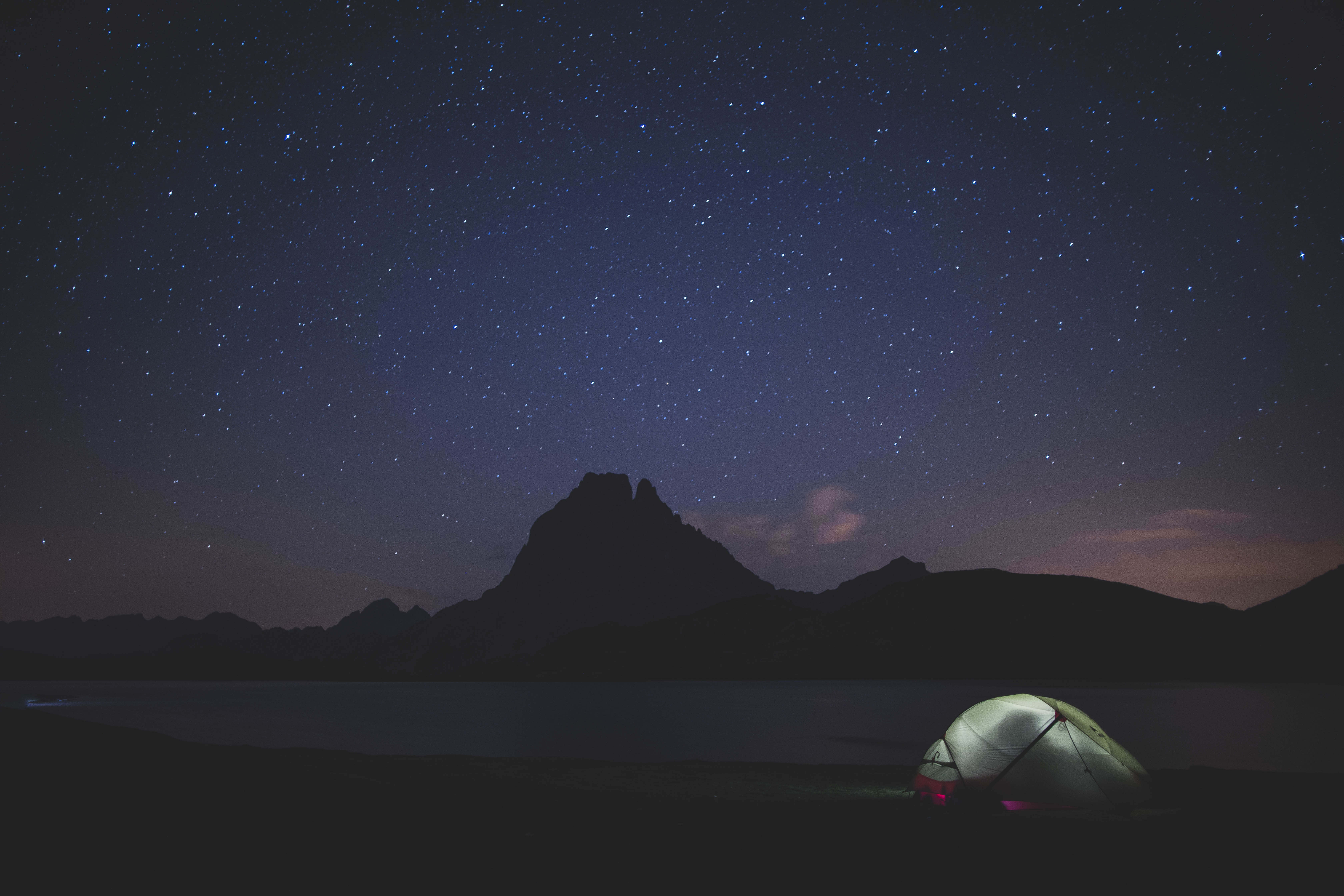 silhouette photography of mountain under cluster of stars