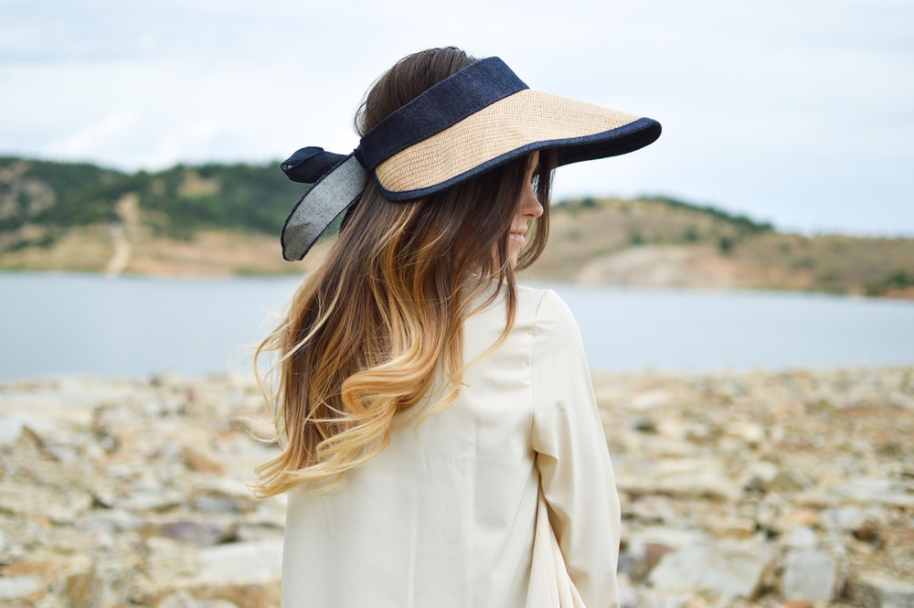 woman standing near lake wearing visor hat