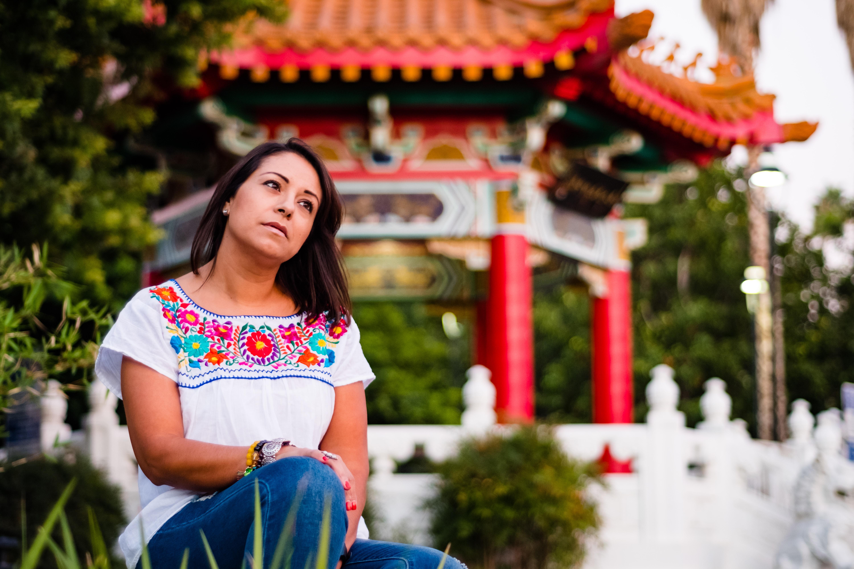 woman sitting near gazebo and green plants