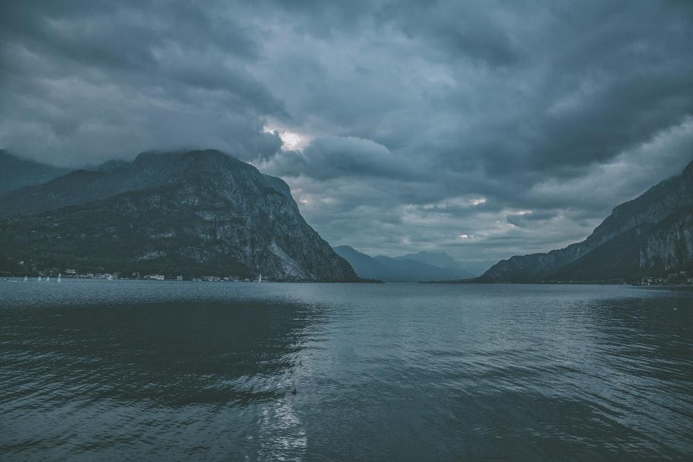 calm sea near mountains under grey sky